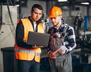 Dois homens analisando sistemas em uma fábrica