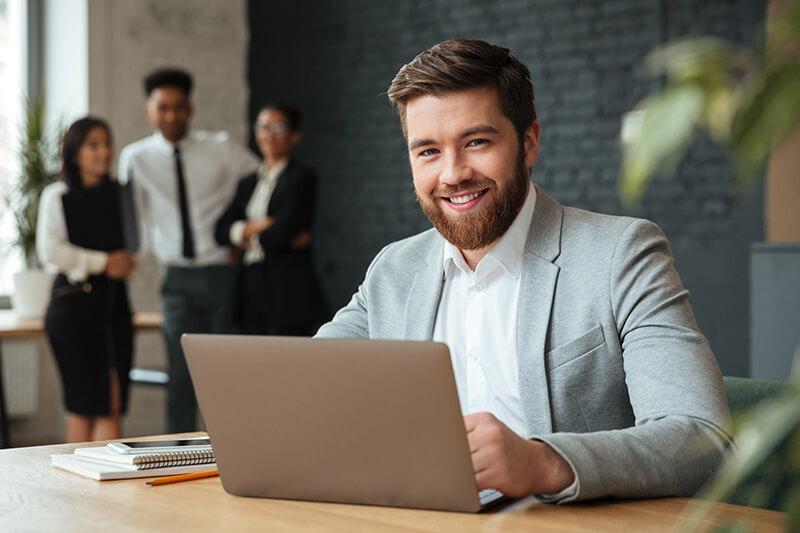 Home usando o computador e sorrindo.