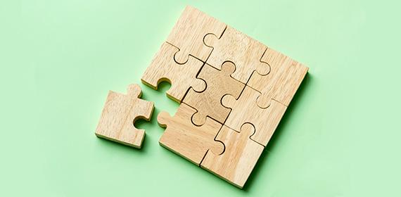 Última peça sendo encaixada em um quebra-cabeça de madeira, representando compatibilidade e integração.