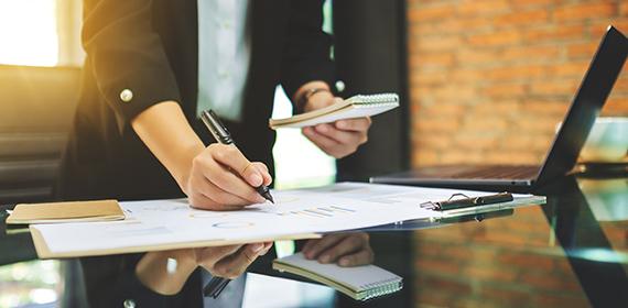 Empresária faz anotações em uma planilha sobre custos de cloud computing.