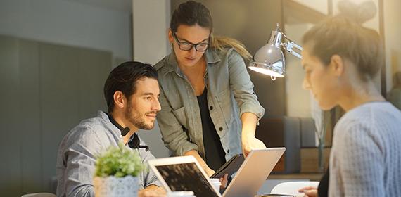 Equipe de duas mulheres e um homem trabalhando com mais produtividade.