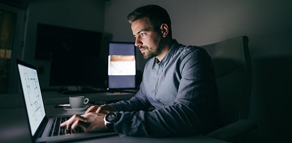 Funcionário trabalhando à noite no computador.