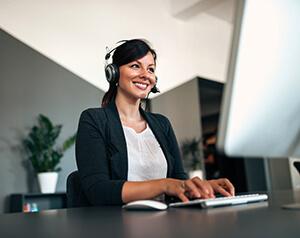 Mulher trabalhando no computador usando uma solução em nuvem.