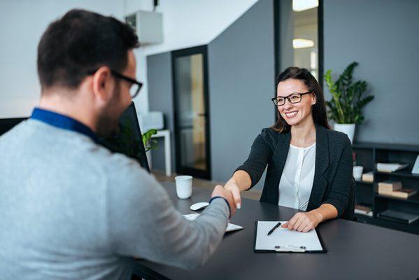 Mulher sorrindo e cumprimentando um homem ao fechar um serviço de migração para cloud.