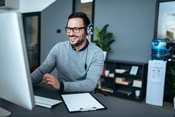Homem sorrindo trabalhando com serviços gerenciados em nuvem.